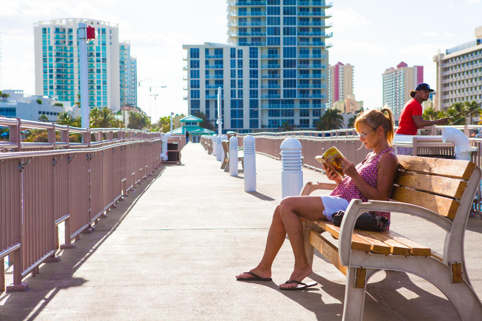Woman Reading On Pier